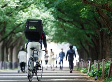 自転車を漕ぐUber Eats配達パートナー