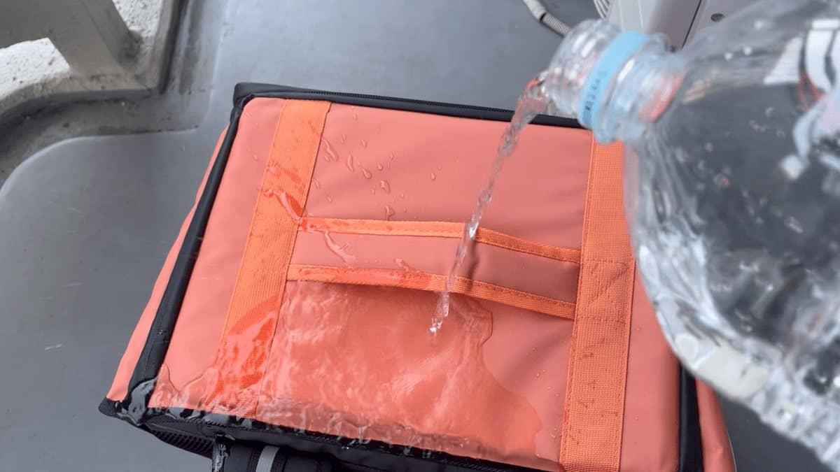 DiDiフード配達バッグに水をかけている(防水性チェック)様子の画像