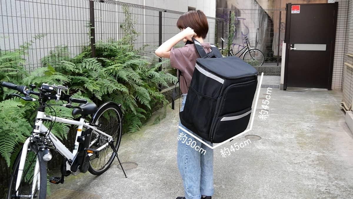 ウーバーイーツのバッグを女性が背負った様子